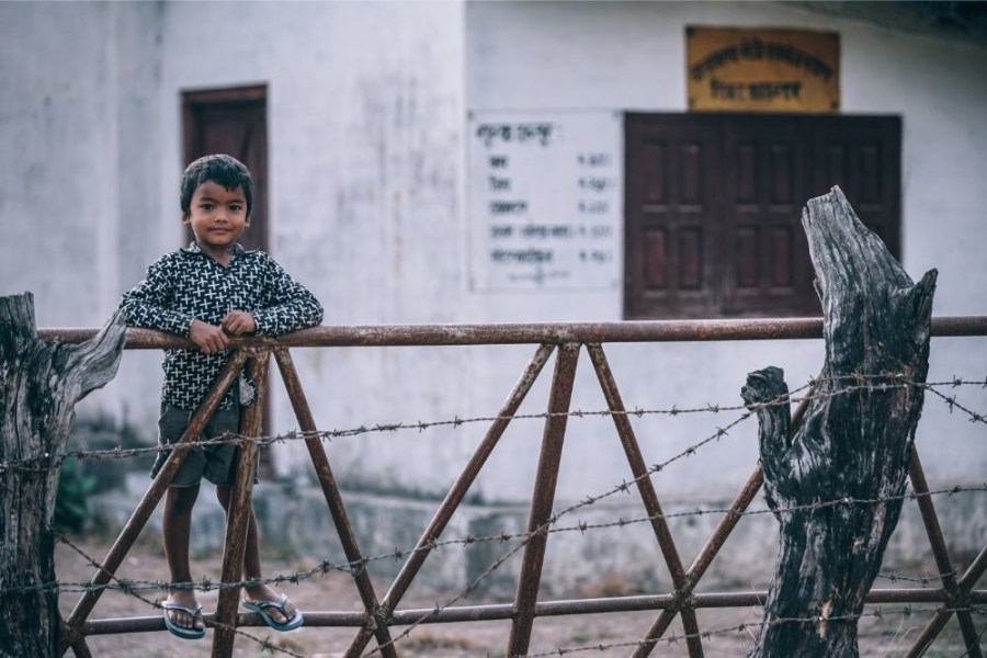 Cute-Nepali-Boy-Standing-at-a-Fence-and-Looking-at-the-Camera