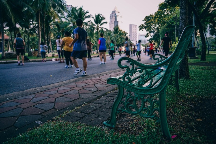 Green-Metal-Park-Bench-with-People-Exercising-in-the-Background