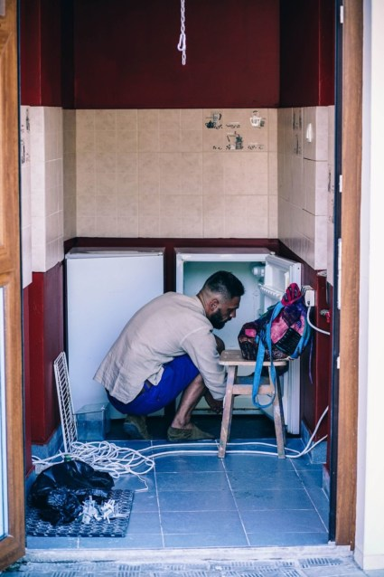 Man-Cleaning-Up-a-Small-Fridge