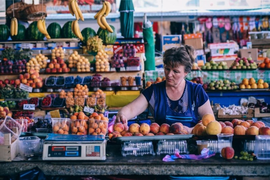 Woman-Carefully-Displaying-Peaches-at-a-Fruit-Store
