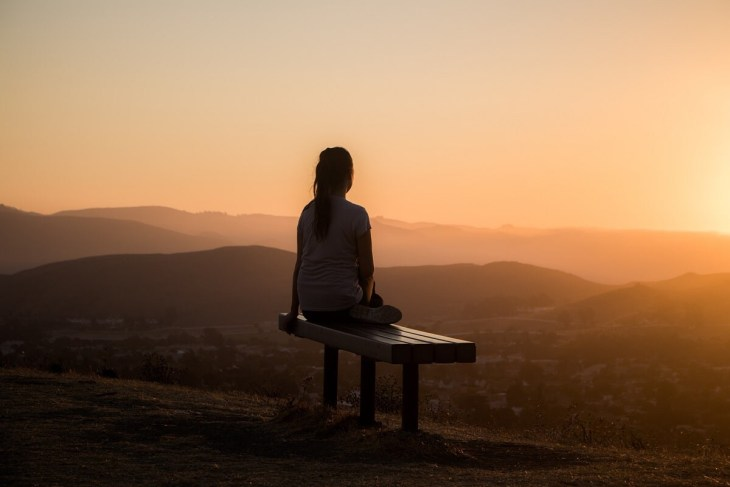 woman meditating during sunset