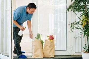 man spraying delivered grocery packages tvekk