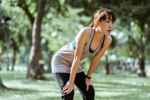 asian woman taking a break from running