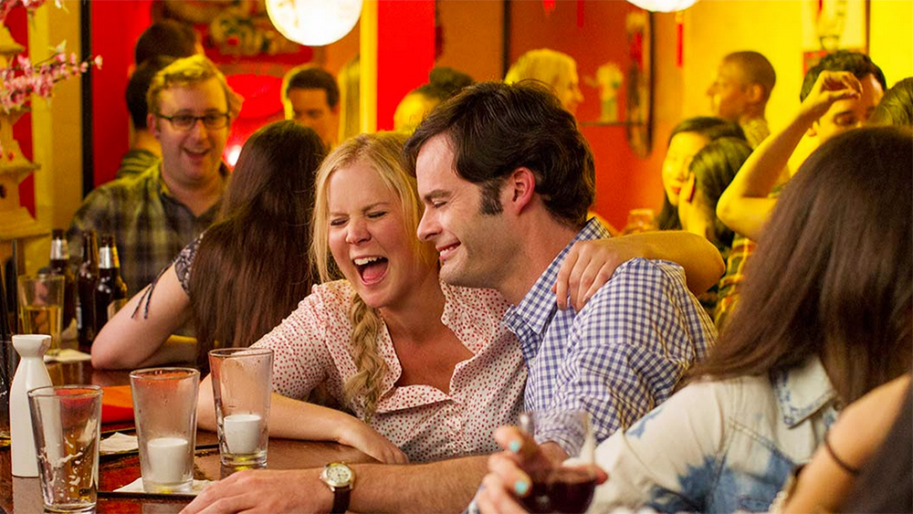 Bill Hader and Amy Schumer laughing at a bar in Trainwreck