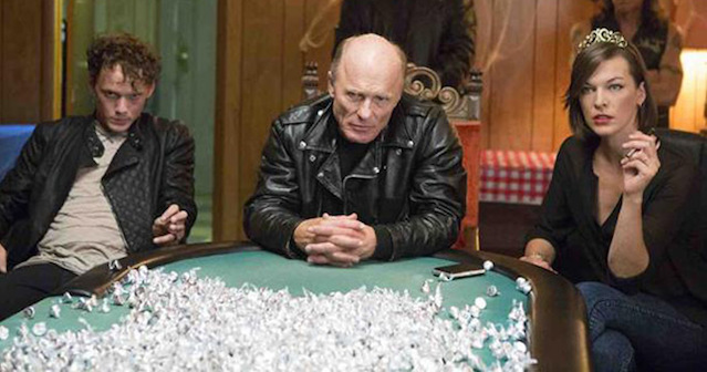 Milla Jovovich, Ed Harris, and Anton Yelchin sitting at a table in Cymbeline