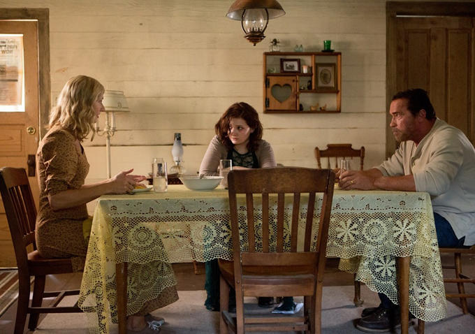 Cast of Maggie movie at dinner table including Arnold Schwarzenegger and Abigail Breslin