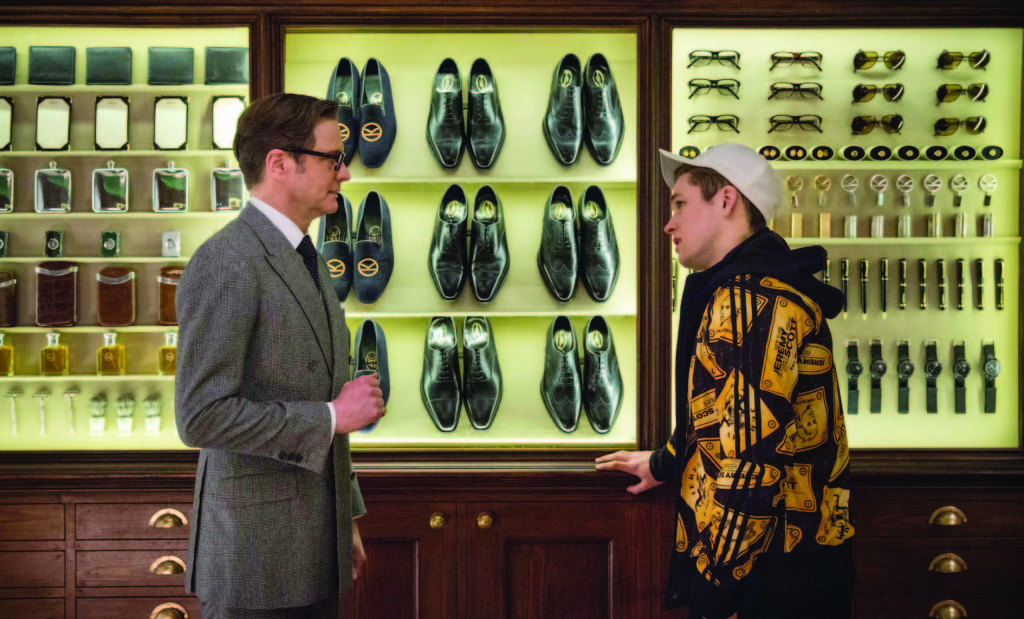 Colin Firth and Taron Egerton standing in front of shoes in Kingsman