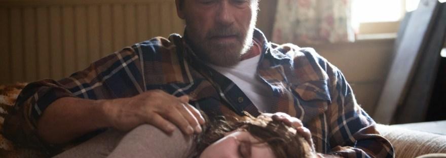Abigail Breslin laying in Arnold Schwarzenegger's lap in Maggie