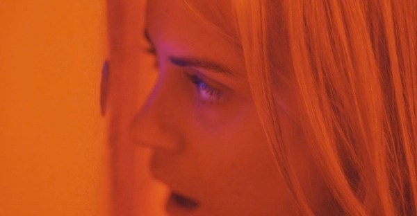 Taylor Schilling looking through peephole in The Overnight