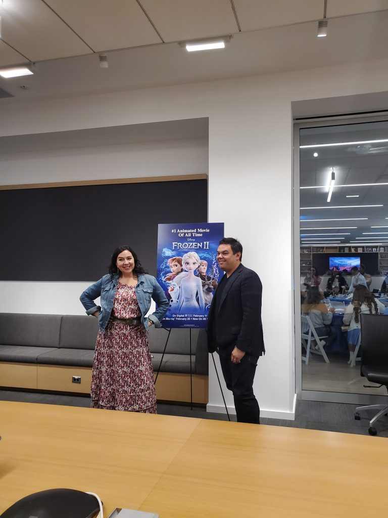 Award-winning songwriters Kristen Anderson-Lopez and Bobby Lopez pose in front of a Frozen II poster