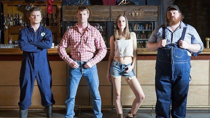 Three men and one woman standing in front of a bar. From left to right: man one in a jumpsuit with his arms crossed, man two in flannel with his thumbs in his pockets, woman in shorts with her thumb through a belt loop, man three in overalls, holding the straps.