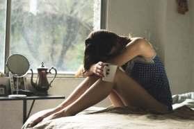 vrouw op bed met haar hoofd op haar kieen en een kopje in haar hand