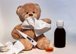 beer met zakdoek voor mond thermometer tussen zijn benen en een flesje medicijnen langs hem. Ziet er ziek uit.