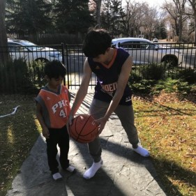 Benjamin teaching Neil how to play basketball.