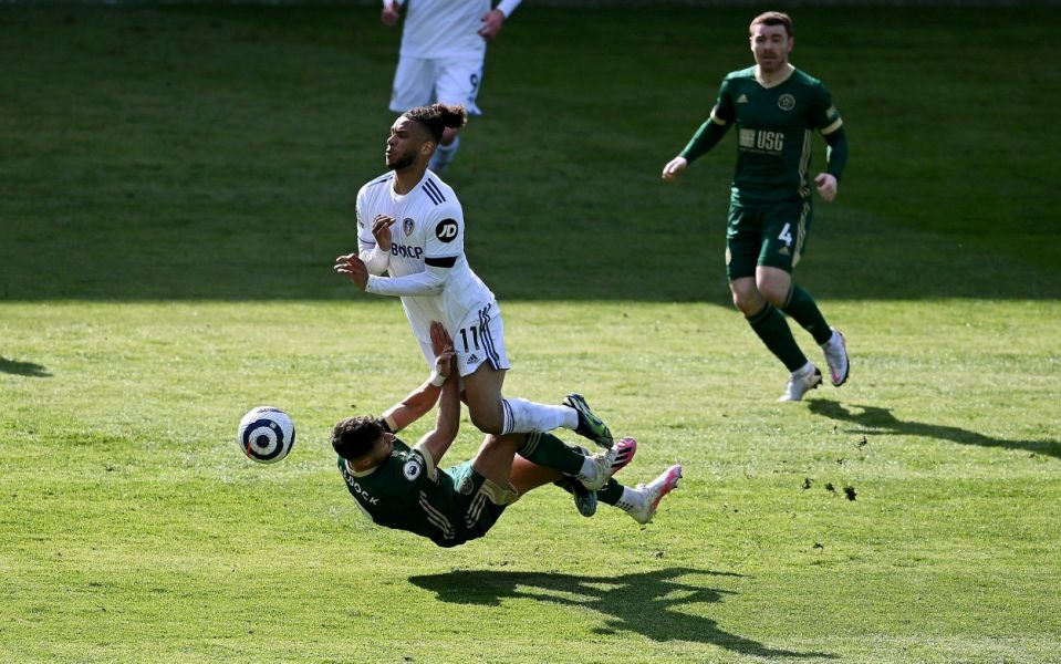 Tyler Roberts of Leeds United is tackled by George Baldock of Sheffield United during the Premier League match between Leeds United and Sheffield United at Elland Road on April 03, 2021 in Leeds, England. - GETTY IMAGES