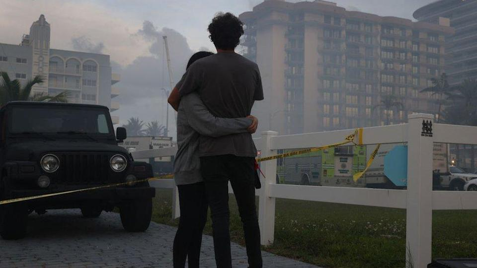 Biviana Faut (L) and Christian Faut comfort each other as they look on at the partially collapsed 12-story Champlain Towers South condo building on June 25, 2021 in Surfside, Florida.