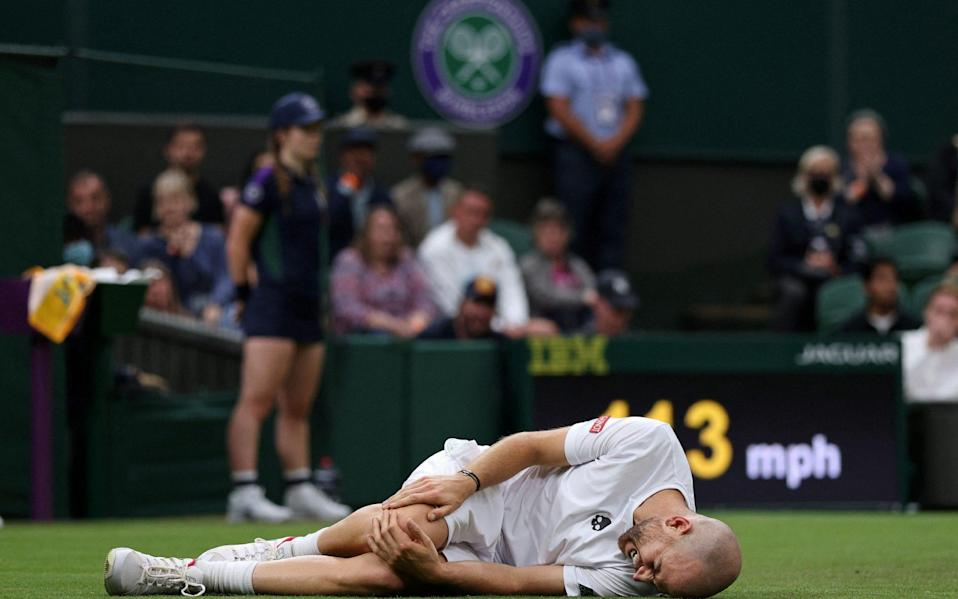 Adrian Mannarino in agony after falling on the Centre Court surface - AFP