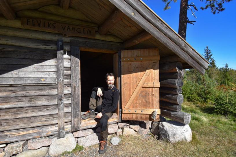 Sittende i døråpningen på Fevikskoia på Romeriksåsene - Oslomarka - Feviksvangen - Åpne koier - Fantastiske marka