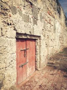 Red door in a fortress wall, Cartagena, Colombia, Fantasy Aisle Travel
