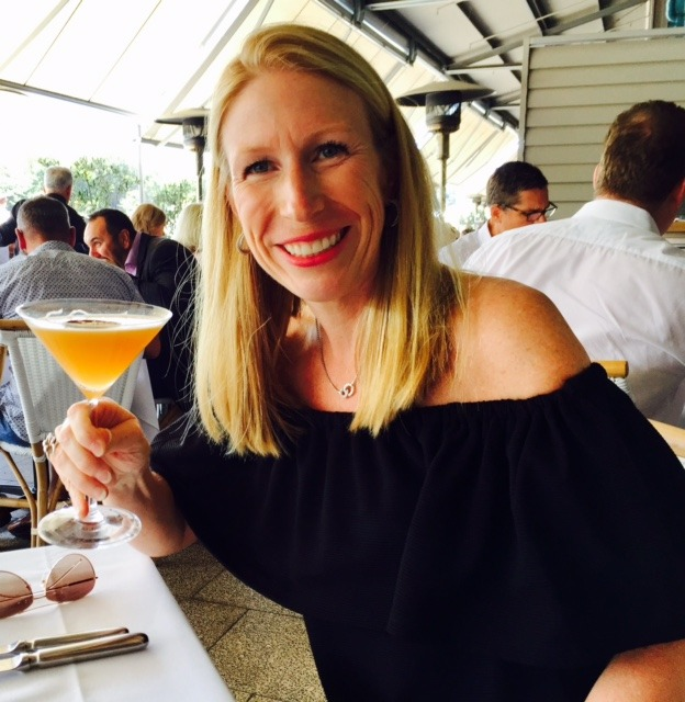 Fantasy Aisle author Kelly Glynn smiling brightly holding a cocktail