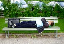 Man in a suit laying on a park bench asleep