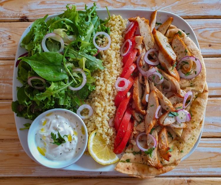 Gyrostallrik med grillad kycklingsfilé, bulgur, äkta grekisk tzatziki, pitabröd, sallad, tomater, rödlök & citronskiva på grekiska lunchrestaurangen Farbror Nikos på Södermalm