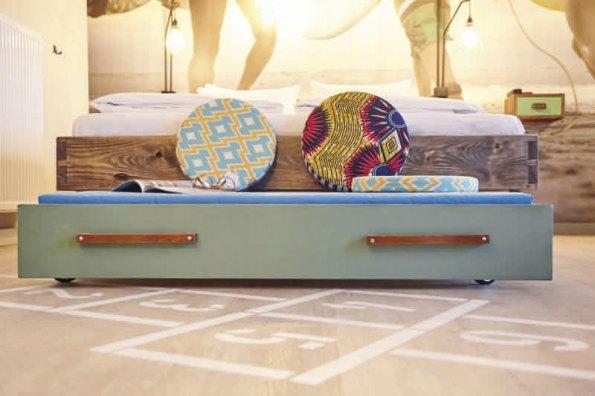 Bettgestell aus Gerüstbohlen mit großem Schubladenelement auf Rollen zum Sitzen und kuscheln. Foto: Beach Motel/Andrea Flak