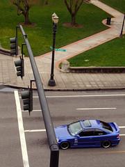 Blue Car at a Red Light near some Green Grass