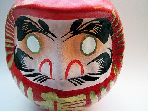 Bodhidharma, the founder of Zen Buddhism represented by this Daruma doll. It is depicted as a red, round head with a mustache, and no eyes.