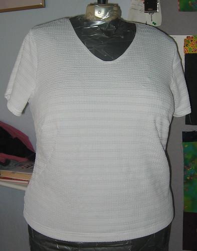 White t-shirt with foldover elastic neck binding.