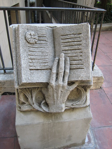 Mysterious hand and book sculpture on the left
