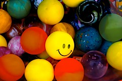smiley face on rubber ball against plain other balls