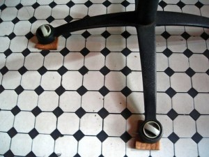 simple machines in the home :: shimmed chair legs on black and white mosaic floor