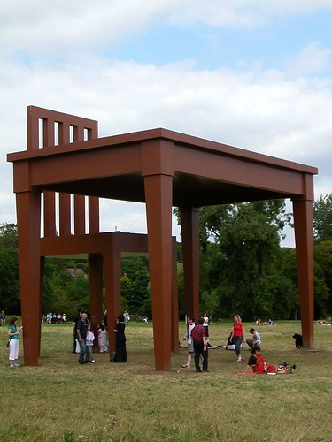 Giant desk and chair with people walking around it