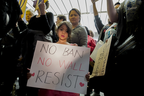 A young girl was holding a sign during a protest at SFO. Protesters gather at the International Terminal's arrival hall at San Francisco International Airport on January 29, 2017 against Trump's Muslim ban.