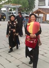 Eine Frau mit dem gut eingepackten Kind auf dem Dorfplatz in Xiangcheng