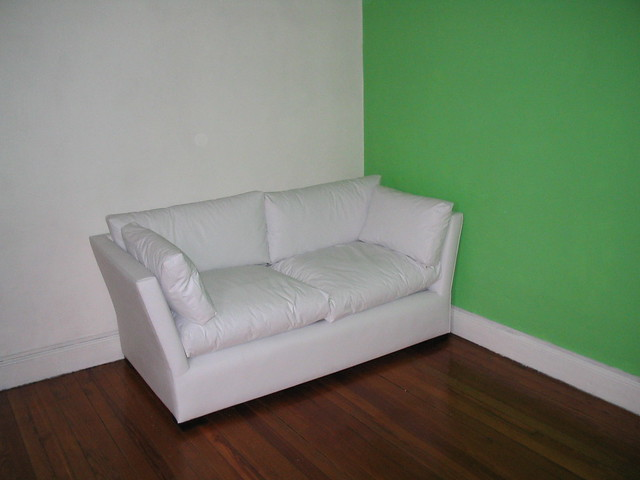 A two-seater sofa against a green wall, a white wall and a wooden floor