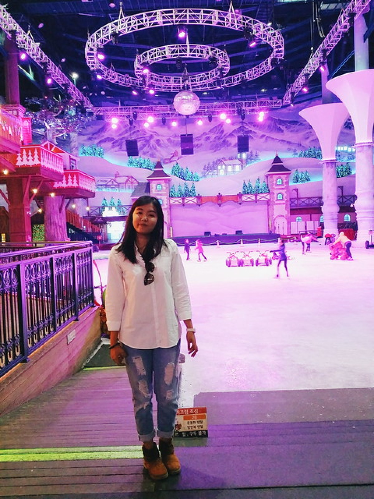 A girl standing with One Mount skating rink on her background
