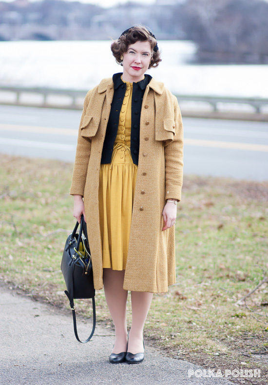Midcentury late winter outfit featuring a tawny yellow overcoat, black jacket, gold dress, and black bag, hat, and shoes.