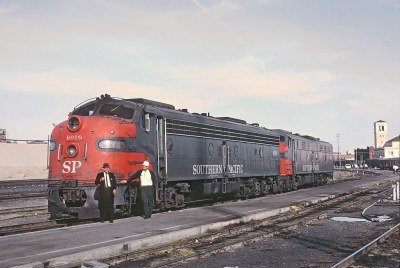 SP E8A 6018 and sister preparing to back on to Train 3, the Sunset Golden State.  Note the number board says #3. Tower of El Paso Texas Union Station in background on March 20, 1967