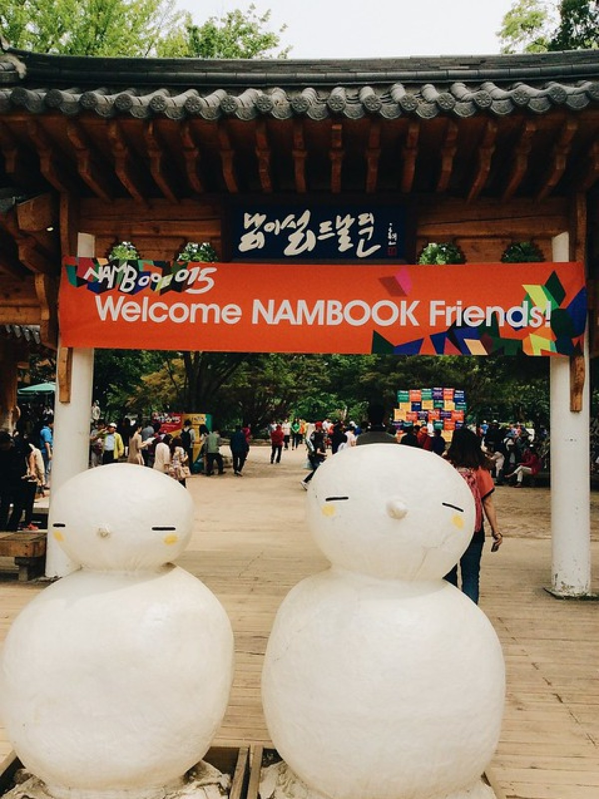 two snowmen in the entrance gate of Nami Island with banner saying Welcome Nambook friends