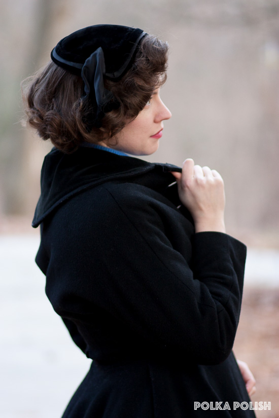 1950s winter ensemble with a black princess coat with velvet trim paired with a velvet cap