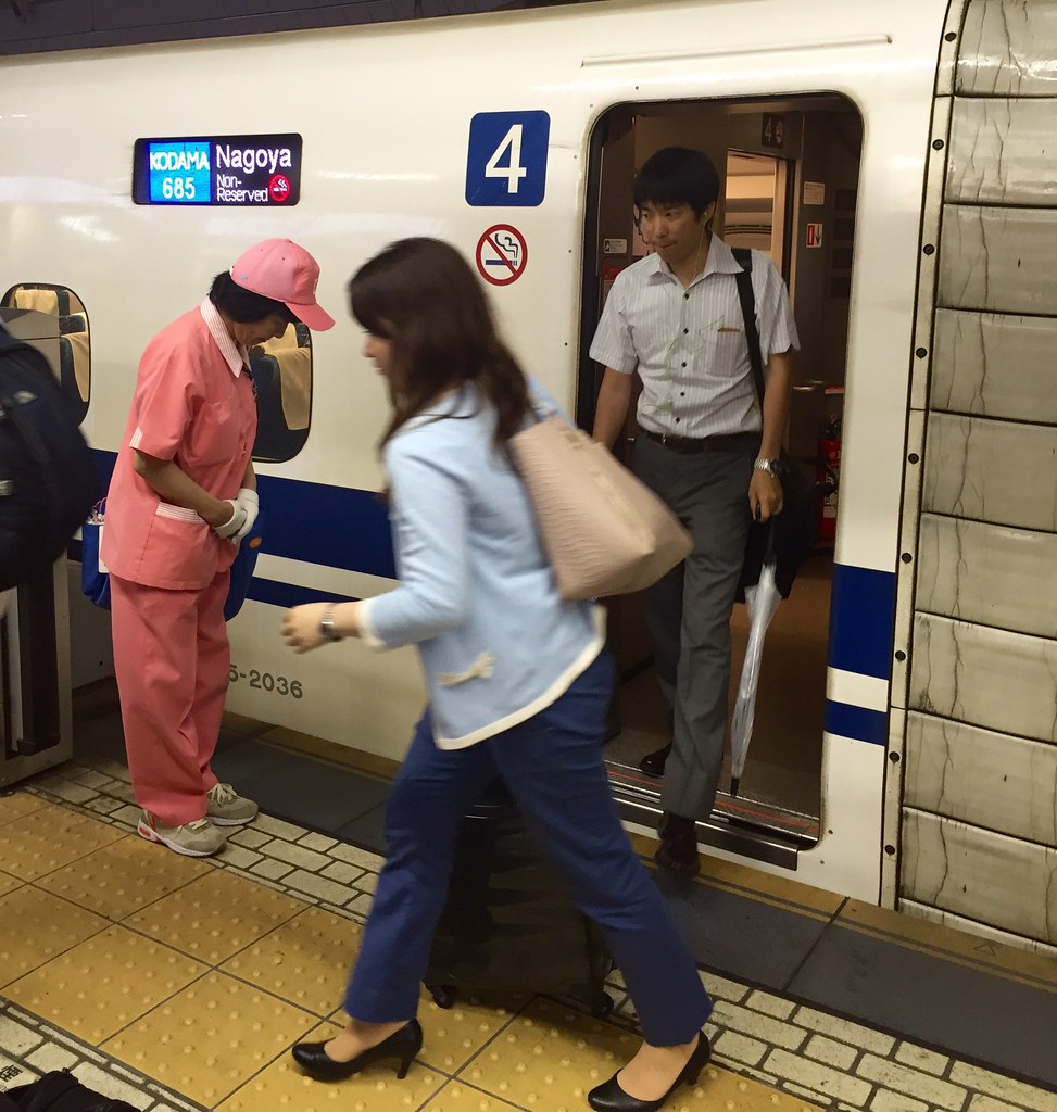 Workers bow to the passengers leaving the Shinkansen