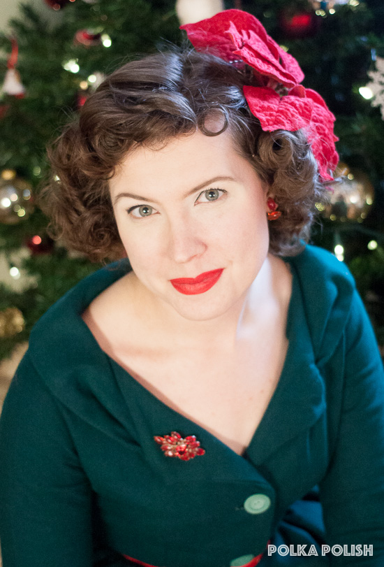 Festive red and green 1950s inspired Christmas holiday outfit featuring a large velvet poinsettia