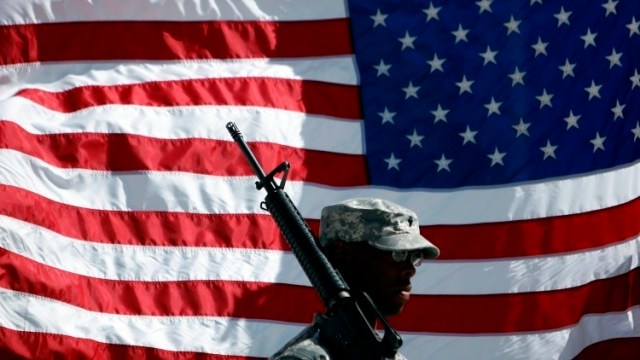 A U.S. soldier holds his rifle in front of a U.S. flag during a Memorial Day observance ceremony at the Bagram airbase, north of Kabul May 25, 2009. REUTERS/Ahmad Masood (AFGHANISTAN MILITARY) - RTXNEAM