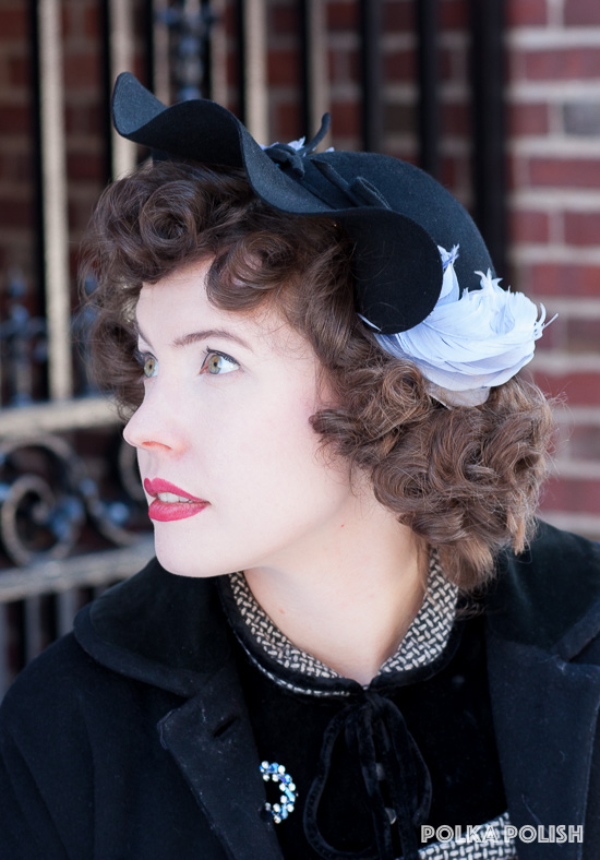 Black vintage wool felt hat with a ruffled brim and swirls of ice blue feathers at the temples
