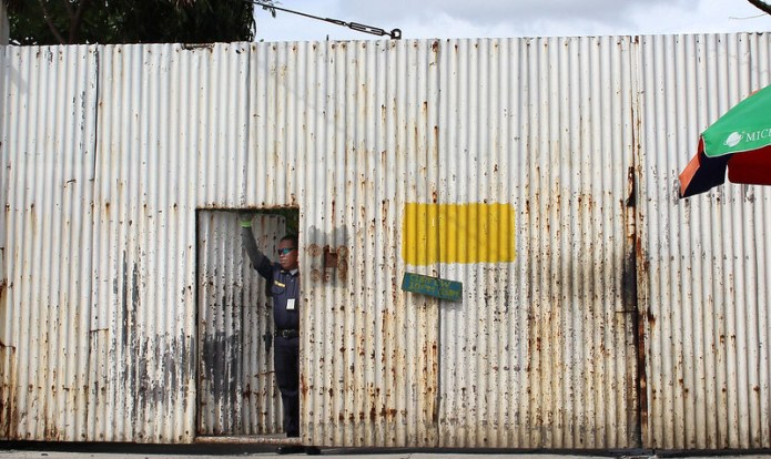 security guard standing by the door of a corrugated tin wall