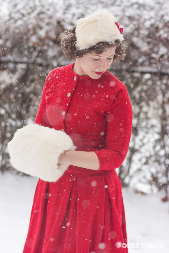 Vintage Christmas outfit featuring a red skirt suit with white fur accessories in the snow