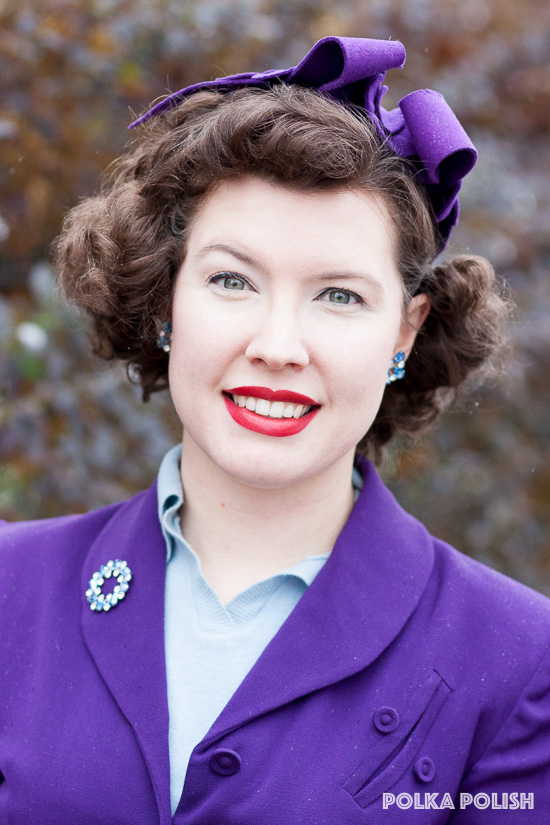 1940s royal purple jacket with asymmetric pocket details paired with ice blue B. David costume jewelry and a purple New York Creations hat