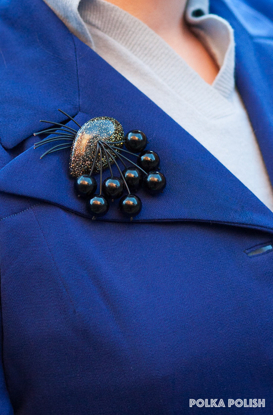Luxulite reproduction confetti glitter and black cherry brooch on the lapel of a vintage 1940s royal blue jacket